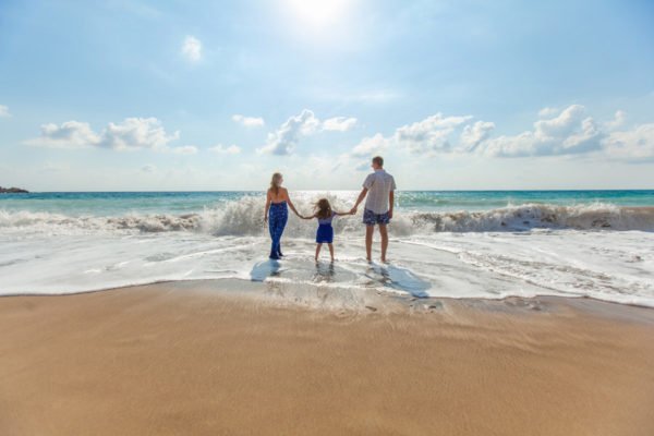 海辺で手をつなぐ3人家族