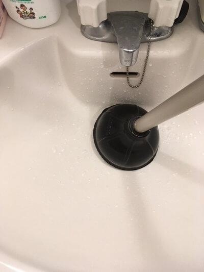 洗面所の詰まりの道具ラバーカップで詰まりを解消する様子